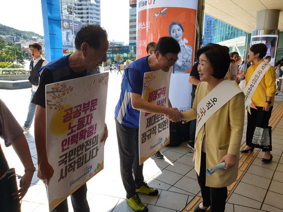 심상정 정의당 대표가 11일 추석 귀성객 인사를 위해 찾은 서울역에서 선전전을 벌이는 민주노총 관계자들과 인사를 나누고 있다. 하준호 기자