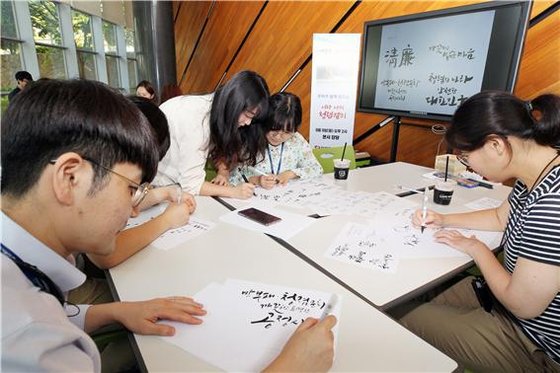 한국동서발전 직원들이 청렴 문구를 담은 캘리그라피를 그리고 있다.