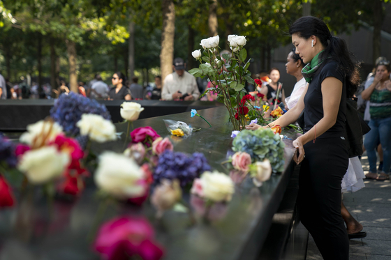 한 시민이 희생자의 이름위에 추모하는 꽃을 놓고 있다. [AP=연합뉴스]