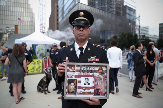에드윈 모랄스가 희생된 동료의 사진을 들고 추모식에 참석했다. [로이터=연합뉴스]