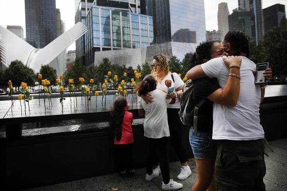 희생자의 유족들이 그라운드 제로에서 서로를 안고 있다. [AFP=연합뉴스]
