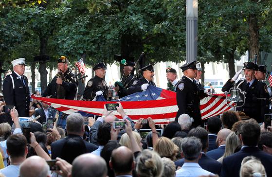 경관들이 미국 국기를 들고 추모식장으로 향하고 있다. [로이터=연합뉴스]