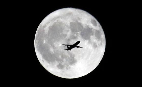 추석인 13일 전국에서 보름달을 볼 수 있을 전망이다. 지난해 추석 연휴였던 9월 25일 오후 성남 분당구 궁내동 하늘에 뜬 보름달 앞으로 항공기가 지나가고 있다. [연합뉴스]