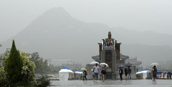 기상청은 연휴 마지막 날인 15일 서울과 경기도를 비롯해 전국 곳곳에서 비가 조금 내리겠다고 예보했다. 사진은 지난 5일 오후 서울 광화문광장에서 시민들이 우산을 쓴채 걸어가고 있는 모습이다. [뉴스1]