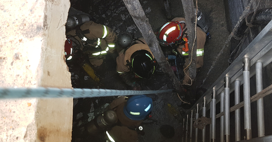 지난 10일 오후 2시30분쯤 경북 영덕군 축산면 오징어 가공업체 지하탱크에 청소 작업을 위해 내려갔던 작업자 4명이 질식해 119 구급대원들이 구조를 하고 있다. [사진 경북도소방본부]