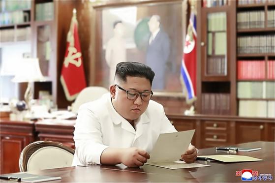 조선중앙통신이 지난 6월 23일 홈페이지에 공개한 사진에서 김정은 북한 국무위원장이 집무실로 보이는 공간에서 트럼프 대통령의 친서를 읽는 모습. [사진 연합뉴스]