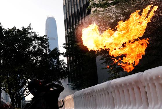 홍콩 반정부 시위대가 15일 홍콩 정부 청사를 향해 화염병을 던지고 있다. [로이터]