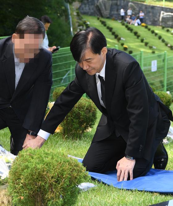"""조국 법무부 장관이 지난 14일 부산추모공원에서 고 김홍영 검사 묘소를 참배하고 있다. 왼쪽은 김 검사의 부친. 조 장관은 '검사 교육 및 승진 제도가 바뀌어야 한다""""고 말했다. 송봉근 기자"""