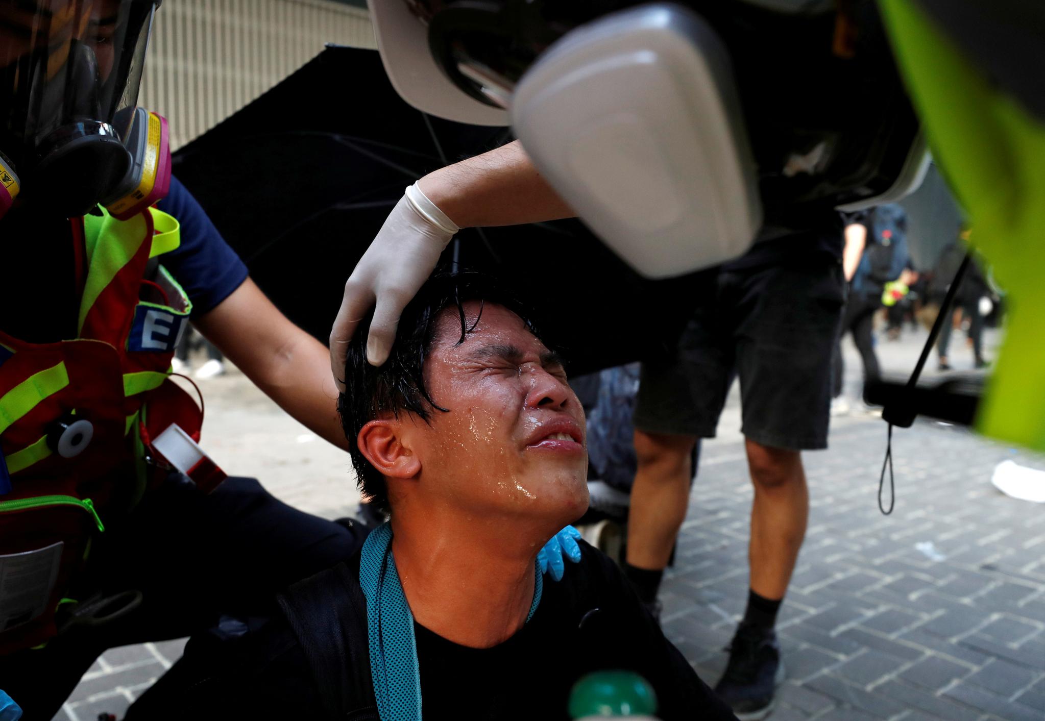 시위대와 경찰간의 격렬한 충돌이 발생한 15일(현지시간) 홍콩 정부중앙청사 인근에서 한 시위대가 경찰이 발사한 최루탄 연기에 눈물을 흘리고 있다. [로이터=연합뉴스]
