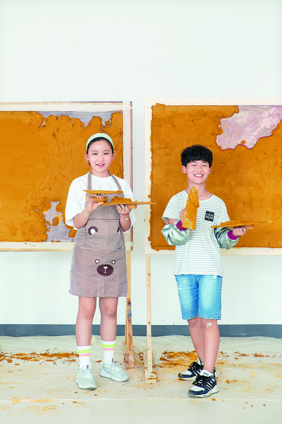 신민서(왼쪽)·김민서 학생기자가 나무판에 직접 미장을 해봤다. 넓지 않은 면적이지만 처음 하는 사람에게는 쉽지 않은 작업이다.