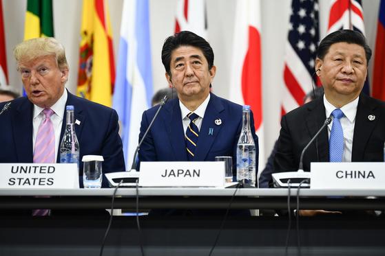지난 6월 28일 일본 오사카에서 열린 주요20개국(G20) 정상회의에 참석한 아베 신조 일본 총리(가운데)가 도널드 트럼프 미국 대통령(왼쪽)과 시진핑 중국 국가주석 사이에 앉아 있다. [AFP=연합뉴스]