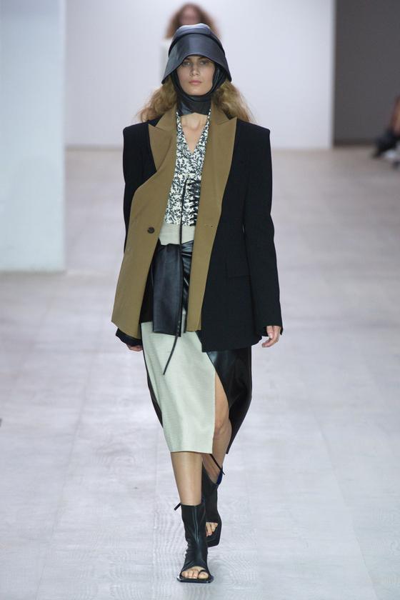 17일 열린 런던패션위크 YCH 2020 봄여름 컬렉션. 코르셋 디테일의 이너 위에 각진 재킷을 걸치고 가죽 소재의 부츠와 모자를 쓰고 걸어나오는 모델. [사진 YCH]