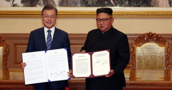 문재인 대통령(왼쪽)과 김정은 국무위원장이 지난해 9월 19일 백화원 영빈관에서 정상회담을 마친 뒤 평양공동선언서에 서명한 후 선언문을 펼쳐보이고 있다. [평양사진공동취재단]