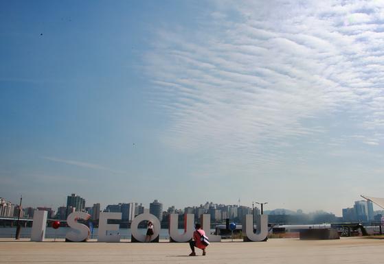 미세먼지 없는 맑은 가을 날씨가 이어지는 지난 2일 오전, 서울 여의도 한강공원을 찾은 연인이 한강을 배경으로 사진을 찍고 있다. [연합뉴스]