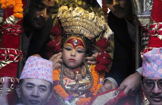 쿠마리가 지난 13일 네팔 카트만두에서 열린 인드라 자트라 축제에 나타났다. 군인들이 축포를 쏘자 한 사제가 쿠마리의 귀를 막아주고 있다. [AP=연합뉴스]