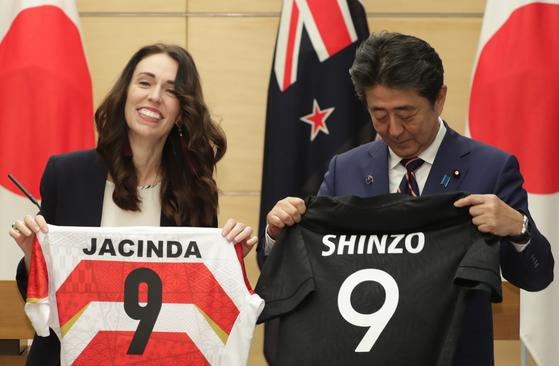 아베 신조 일본 총리가 10일 저신다 아던 뉴질랜드 총리와 선수 유니폼을 교환한 뒤 'SHINZO 9' 적힌 등번호를 보고 있다. [사진 지지통신]