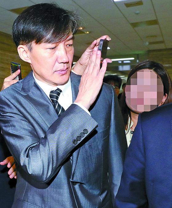조국 장관이 19일 국회에서 정동영 민주평화당 대표를 만난 후 본청을 떠날 때 취재진의 휴대전화가 얼굴에 닿자 손으로 막고 있다. [뉴시스]