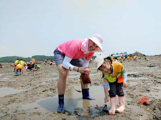 경기도 화성시 백미리 에서 관광객들이 조개를 캐 고 있다. [사진 백미리어촌계]