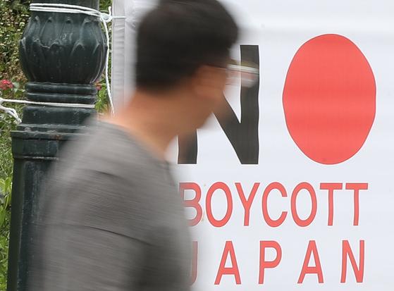 지난달 6일 일본 불매운동 펼침막 옆을 한 시민이 지나가고 있다. [연합뉴스]