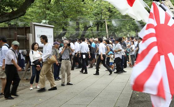 일본의 패전일이자 한국의 광복절인 15일 일본 도쿄(東京) 야스쿠니신사(靖國神社)에서 전범기인 욱일기(旭日旗)가 휘날리는 가운데 참배객들이 걸어가고 있다. [연합뉴스]