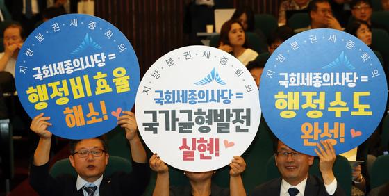 20일 서울 여의도 국회 도서관에서 열린 국회 세종의사당 설치를 위한 심포지엄에서 참석자들이 '국가균형발전실현'을 위해 '국회 세종의사당 '설치'를 촉구하는 손팻말을 들고 있다. [뉴스1]