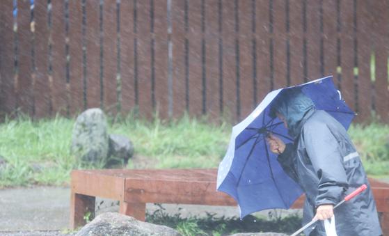 제주가 태풍 타파의 영향을 받은 21일 한라산 어리목 광장에서 우산을 든 한 시민이 강한 비바람에 힘겹게 걸어가고 있다.[연합뉴스]