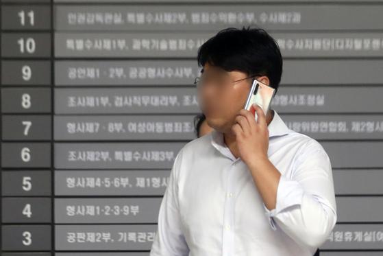 사모펀드 운용사 코링크프라이빗에쿼티(PE) 이상훈 대표가 17일 오후 서울 서초구 서울중앙지방검찰청에서 검찰 조사를 위해 출석, 전화통화를 하고 있다.  이 씨는 조국 장관 5촌 조카 조범동씨 등과 함께 WFM·웰스씨앤티 등 투자기업 자금 50억원가량을 빼돌린 혐의를 받고 있다. [뉴스1]