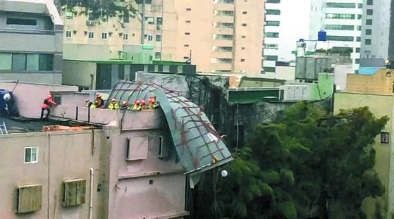 제17호 태풍 '타파'가 북상 중인 22일 부산 해운대구 한 건물 옥상에 철제 구조물이 떨어져 소방관들이 안전조치를 하고 있다. [연합뉴스]