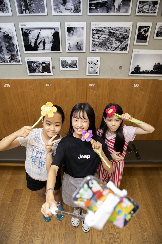 김은비 학생기자와 하람, 이수안 학생모델(왼쪽부터)이 하람이 준비한 유행 물건을 들어 보였다. 하람은 셀카봉을 길게 뽑아 손에 들고었다. 그는 소품을 이용한 셀카는 다양한 색감이 더해져 멋지다고 강조했다.