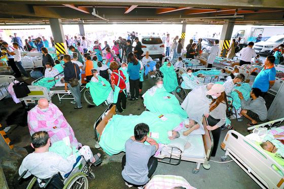 경기도 김포시의 한 요양병원에서 24일 화재가 발생해 입원 환자 132명 중 2명이 숨지고 47명이 다쳤다. 화재 발생 후 인근 주차장으로 대피한 환자들이 병원 호송차량을 기다리고 있다. [뉴스1]