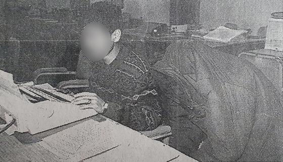 화성연쇄살인사건의 유력한 용의자로 지목된 이모씨(오른쪽)가 1994년 충북 청주에서 처제를 성폭행한 뒤 살해한 혐의로 검거돼 옷을 뒤집어쓴 채 경찰조사를 받고 있는 모습. [연합뉴스]