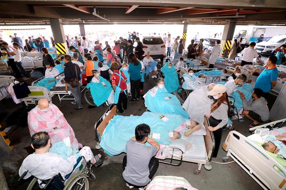24일 오전 9시 3분쯤 경기 김포시 풍무동의 한 요양병원에서 화재가 발생, 긴급대피한 환자들이 치료를 받고 있다. [뉴스1]