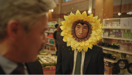 "tvN 금요드라마 '쌉니다 천리마마트'. 마트 사장 정복동(김병철)이 '오늘 하루 다같이 꽃이 되자""며 해바라기 꽃탈을 쓴 모습이다. [방송캡처]"