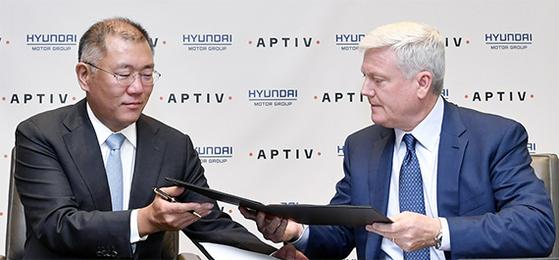 """정의선 현대차그룹 수석부회장(왼쪽)과 케빈 클락 앱티브 최고경영자(CEO)가 23일(현지시간) 미국 뉴욕 골드만삭스 본사에서 자율주행 소프트웨어 개발을 위한 합작법인 설립 본계약에 서명하고 있다. 정 부회장은 '2030년쯤 본격적으로 자율주행차 시대가 열릴 것""""이라고 말했다. [사진 현대차]"""