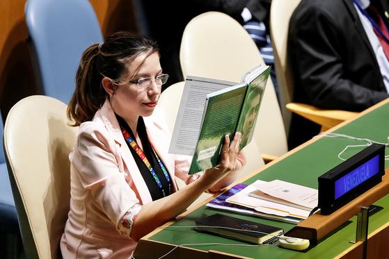 베네수엘라 유엔 대표부 소속 다니엘라 로드리게스가 24일(현지시간) 미국 뉴욕에서 열린 유엔총회에서 도널드 트럼프 미국 대통령이 연설하는 동안 책을 보고 있다. [로이터=연합뉴스]