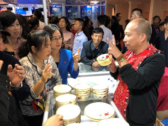 평양가을철국제상품전람회가 25일 평양체육관에서 열렸다. 주부들이 그릇을 판매하는 중국인 바이어와 손가락 대화를 하고 있다.[타스=연합뉴스]