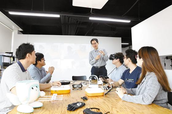 최용근(대학원 컴퓨터학과 교수·가운데) 단국대학교 웨어러블산업센터장이 학생들에게 첨단 웨어러블 기기에 관해 설명하고 있다. [사진 단국대]