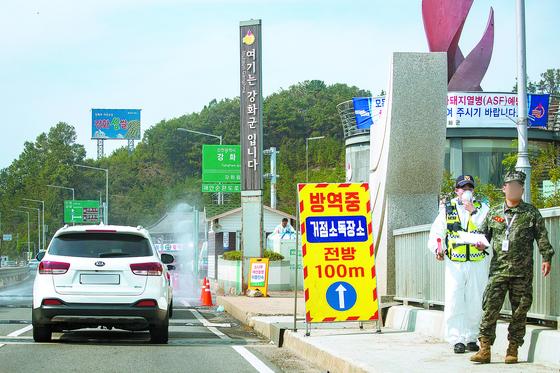아프리카돼지열병(ASF) 확진 판정이 이틀 연속 이어진 인천 강화도에서 25일 방역 관계자들이 돼지열병 확산을 막기 위해 강화대교를 오가는 차량들에 대한 소독을 하고 있다. [뉴스1]