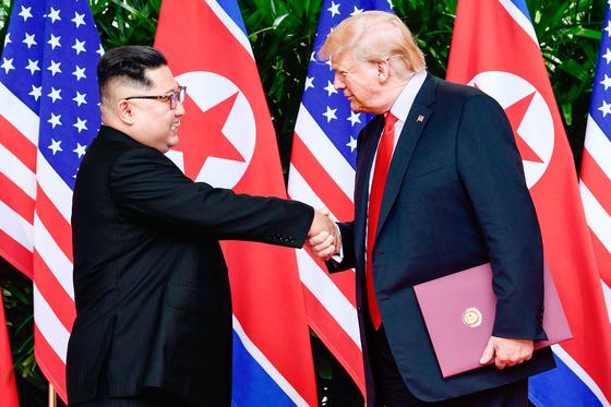 김정은 북한 국무위원장(왼쪽)과 도널드 트럼프 미국 대통령이 지난달 6월 12일(현지시간) 싱가포르 센토사 섬 카펠라 호텔에서 140여 분에 걸친 단독·확대 정상회담과 업무오찬을 가졌다. 양국 정상이 각각 서명한 합의문을 교환한 뒤 헤어지며 악수하고 있다. [사진 연합, AFP]