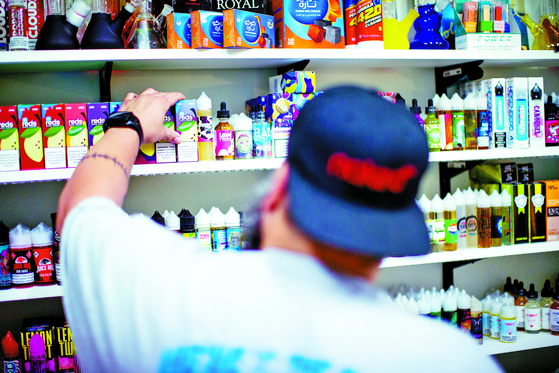 지난 12일 미국 뉴저지 주의 한 상점 점원이 전자담배를 정리하고 있다. 보건복지부는 미국 정부가 액상형 전자담배 판매 금지 계획을 발표하자 지난 20일 사용자제를 권고했다. [로이터]