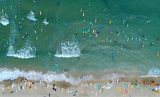 강원도 양양에서는 가을 서핑을 즐기는 사람이 많다. 여름보다 파도 질이 좋고 바닷물이 차지 않다는 걸 아는 사람이 늘면서다. 오는 10월 11~13일 죽도 해변에서 '양양 서핑 페스티벌'도 열린다. 드론으로 촬영한 죽도 해변. 김경빈 기자