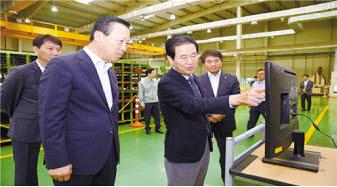 '동반자 금융'을 강조하는 김도진 기업은행장(왼쪽 첫 번째)이 거래 기업의 생산공장을 방문해 제품 설명을 듣고 있는 모습. [사진 IBK기업은행]