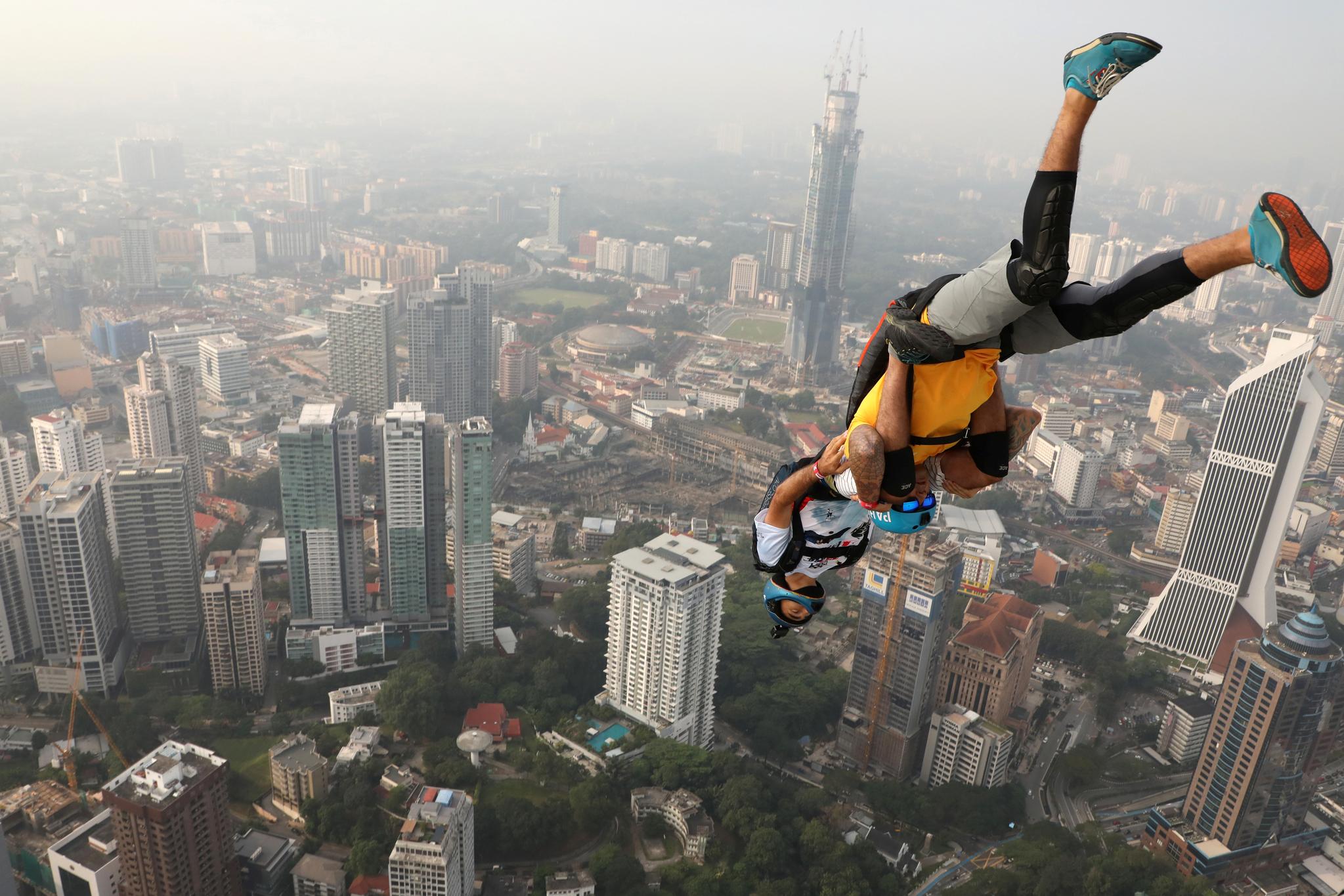 26일(현지시간) 말레이시아 쿠알라룸푸르에서 열린 '인터내셔널 점프 말레이시아 2019' 행사에서 베이스 점퍼가 쿠알라룸푸르 타워에서 뛰어내리고 있다. 베이스 점핑은 건물이나 다리 등 높은 건물에서 낙하산을 타고 내려오는 스포츠다. [로이터=연합뉴스]