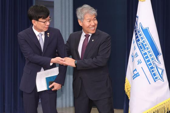 김수현 전 대통령비서실 정책실장(오른쪽)이 지난 6월 21일 신임 김상조 실장과 손을 잡고 인사를 나누고 있다. [중앙포토]