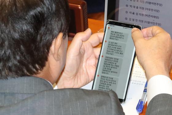 """주광덕 자유한국당 의원이 26일 오후 서울 여의도 국회 본회의장에서 열린 정치 분야 대정부질문에서 항의성 문자를 확인하고 있다. 이날 주 의원이 받은 문자에는 """"님은 계속 검사들로부터 조국 장관 수사에 대해서 누구한테 보고를 받고 있습니까? 그것도 불법 아닌가요?"""" 등의 내용이 담겨 있다. [뉴스1]"""