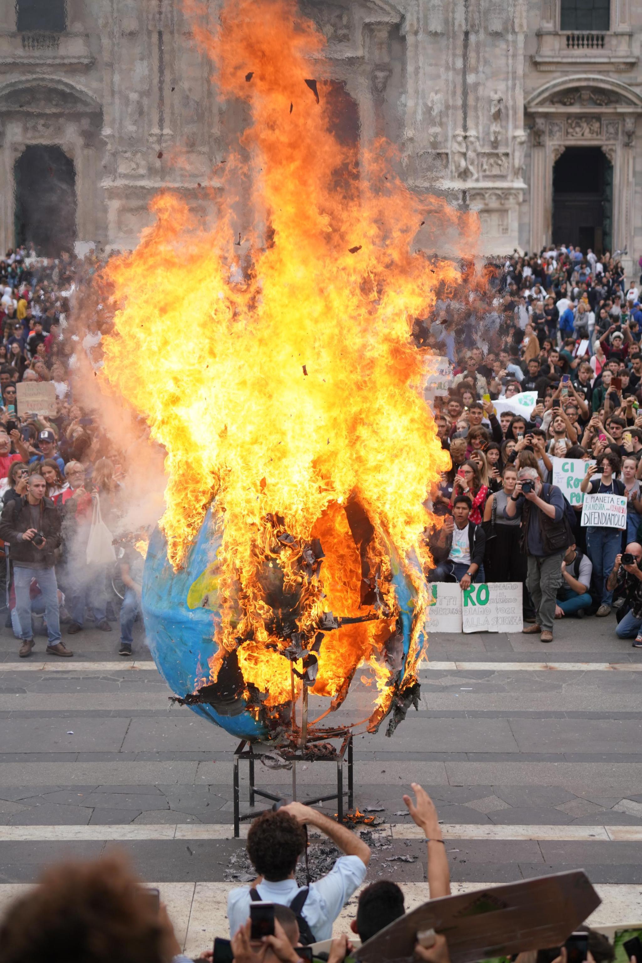 27일(현지시간) 이탈리아 밀라노에서 열린 기후변화 대응 집회에 참여한 시민들이 지구 온난화에 대한 위기감을 고조시키기 위해 지구본 모형을 불태우고 있다. 이날 전세계 곳곳에서 기후변화에 대응을 촉구하는 집회가 동시에 열렸다. [EPA=연합뉴스]
