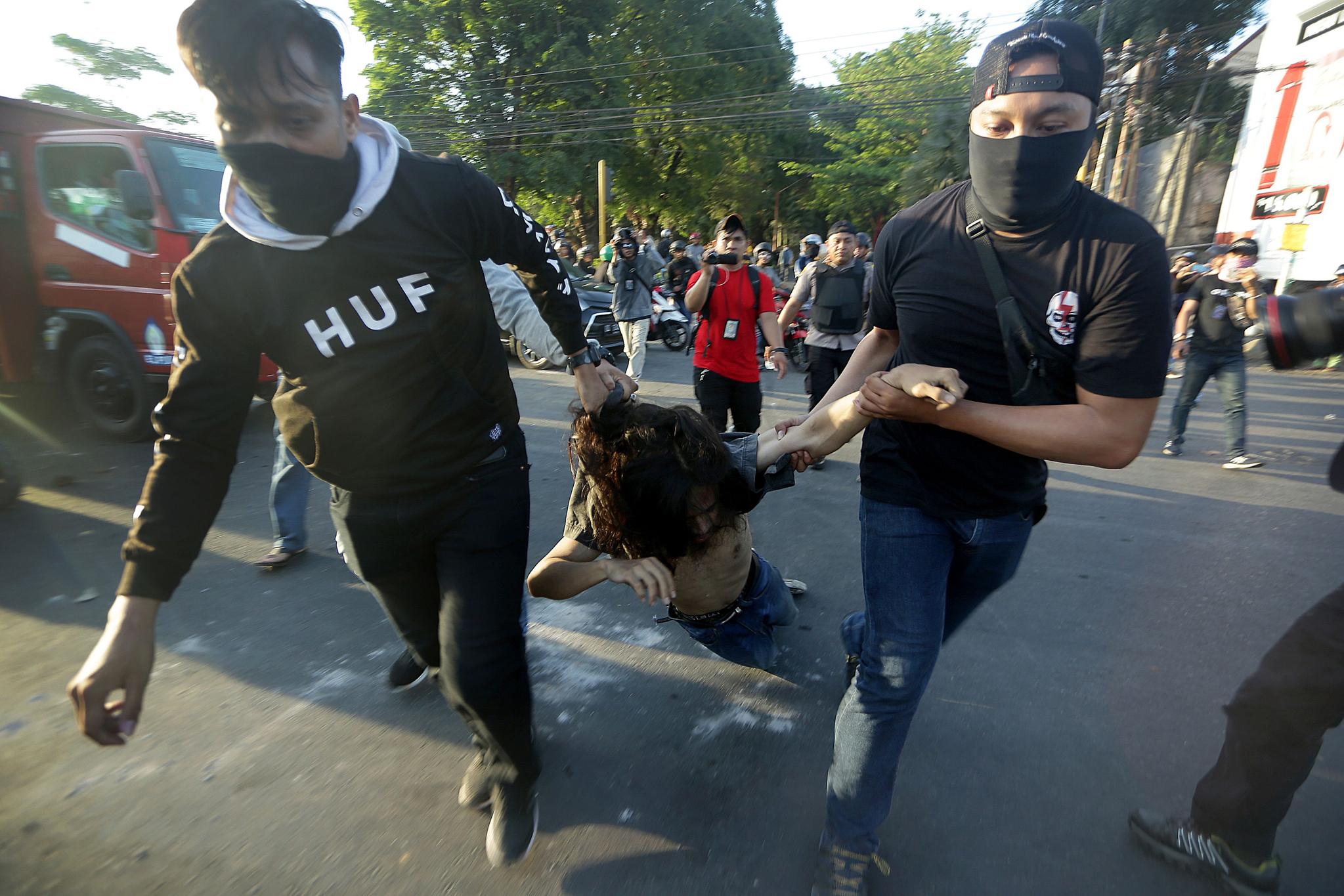 26일(현지시간) 인도네시아 술라웨시 마카사르의 대학 캠퍼스 앞에서 한 시위자가 사복 경찰에게 끌려가고 있다. [AFP=연합뉴스]