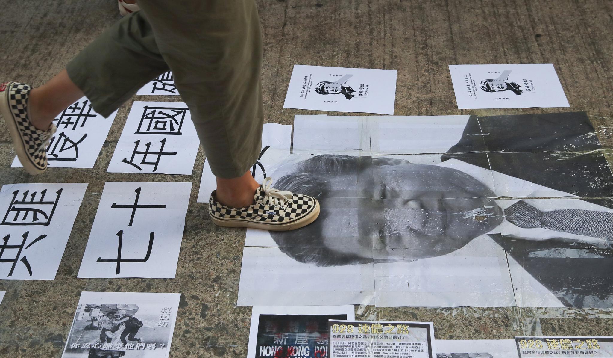 홍콩 '우산혁명' 5주년 기념집회가 열린 28일(현지시간) 시민들이 홍콩 시내 바닥에 붙은 시진핑 중국국가 주석의 포스터 사진을 밝고 지나가고 있다. [EPA=연합뉴스]