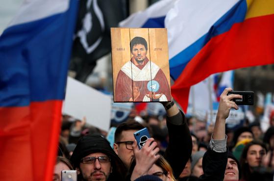 2019년 3월 10일, 러시아 모스크바에서 국가의 인터넷 통제에 항의하는 시위가 열렸다. 한 시민이 텔레그램을 개발한 파블 듀로프의 초상을 들고 있다. 그는 러시아에서 자유와 저항의 상징으로 인식된다. [로이터=연합]