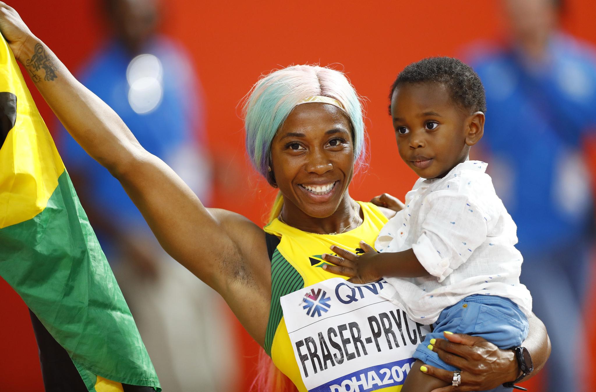 자메이카의 셸리 앤 프레이저-프라이스가 29일 여자 100m 결승에서 우승한 뒤 아들 지온을 안고 트랙을 돌고 있다. [REUTERS=연합뉴스]